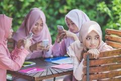 Chica joven que usa su propio smartphone e ignorando a su amigo Foto de archivo