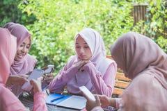 Chica joven que usa su propio smartphone e ignorando a su amigo Imagenes de archivo