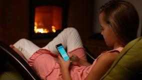 Chica joven que usa su smartphone que se sienta en una mecedora almacen de metraje de vídeo