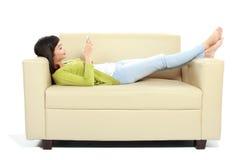 Chica joven que usa su teléfono móvil en el sofá Fotografía de archivo libre de regalías