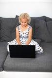 Chica joven que usa una computadora portátil en el país Imagen de archivo libre de regalías
