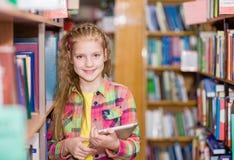 Chica joven que usa una tableta en una biblioteca Fotos de archivo libres de regalías