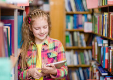 Chica joven que usa una tableta en una biblioteca Imágenes de archivo libres de regalías