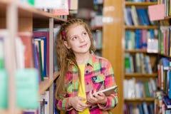 Chica joven que usa una tableta en una biblioteca Fotos de archivo