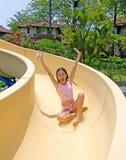Chica joven que va abajo de la diapositiva en la piscina Imagenes de archivo