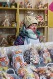 Chica joven que vende el pan de jengibre en mercado de la Navidad de Vilna en el advenimiento Fotografía de archivo