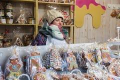 Chica joven que vende el pan de jengibre en mercado de la Navidad de Vilna durante advenimiento Fotografía de archivo libre de regalías