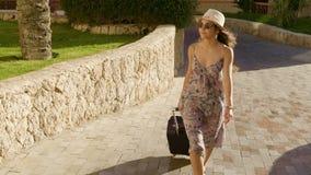Chica joven que viaja en la calle con la maleta metrajes