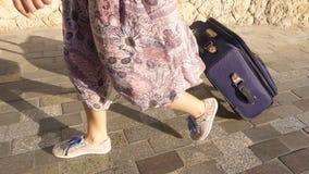 Chica joven que viaja en la calle con su maleta, cámara lenta metrajes