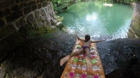Chica joven que viene abajo la cascada en el colchón flotante almacen de video