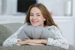 Chica joven relajada que abraza el amortiguador en el sofá Imágenes de archivo libres de regalías