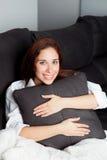 Chica joven relajada que abraza un amortiguador Foto de archivo libre de regalías