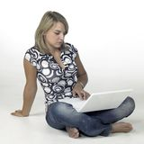 Chica joven relajada que se sienta en la tierra mientras que computa Foto de archivo libre de regalías