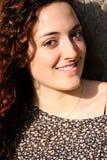 Chica joven rizada, hermosa con sonrisa agradable Fotos de archivo