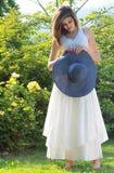 Chica joven romántica con el sombrero y la margarita azules del heno Imagen de archivo libre de regalías