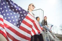 Chica joven rubia con la bandera americana que coloca a los amigos cercanos que se divierten Imágenes de archivo libres de regalías