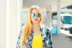 Chica joven rubia del retrato que lleva una camisa a cuadros y las gafas de sol Fotografía de archivo libre de regalías