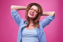 Chica joven satisfecha que se coloca con las manos detrás de la cabeza Imagenes de archivo