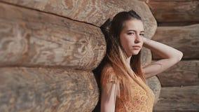 Chica joven sensual hermosa con el pelo largo y en un vestido que presenta cerca de una pared de madera de registros anchos Relaj metrajes