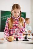 Chica joven seria que usa el microscopio Imagen de archivo