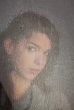 Chica joven sola pensativa en la ventana Foto de archivo libre de regalías
