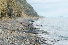 Chica joven sola que se sienta en la orilla entre la roca y el mar Fotografía de archivo