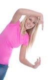 Chica joven sonriente aislada en la camisa rosada que presenta con el finger Imagenes de archivo