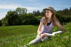 Chica joven sonriente con el libro que descansa en un campo hermoso de la hierba que goza de Sunny Spring Day hermoso Fotografía de archivo