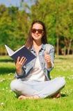 Chica joven sonriente con el libro que se sienta en hierba Imagen de archivo