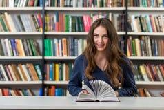 Chica joven sonriente con el pelo oscuro largo flojo que se sienta en un escritorio Fotografía de archivo libre de regalías