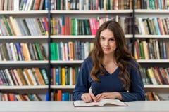 Chica joven sonriente con el pelo oscuro largo flojo que se sienta en un escritorio Foto de archivo