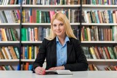 Chica joven sonriente con el pelo rubio que se sienta en un escritorio en el li Fotos de archivo