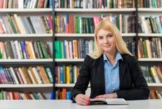 Chica joven sonriente con el pelo rubio que se sienta en un escritorio en el li Foto de archivo