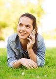 Chica joven sonriente con el smartphone que miente en hierba Imagen de archivo