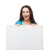 Chica joven sonriente con el tablero blanco en blanco Fotografía de archivo libre de regalías