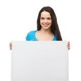 Chica joven sonriente con el tablero blanco en blanco Foto de archivo