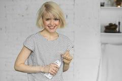 Chica joven sonriente con la botella de agua chispeante Fotos de archivo