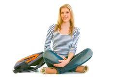 Chica joven sonriente con la cartera que se sienta en suelo Fotografía de archivo libre de regalías