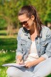 Chica joven sonriente con la escritura del cuaderno en parque Imagenes de archivo