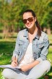 Chica joven sonriente con la escritura del cuaderno en parque Imagen de archivo