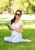 Chica joven sonriente con la PC de la tableta que se sienta en hierba Imagen de archivo