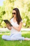 Chica joven sonriente con la PC de la tableta que se sienta en hierba Fotos de archivo