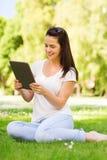 Chica joven sonriente con la PC de la tableta que se sienta en hierba Foto de archivo libre de regalías
