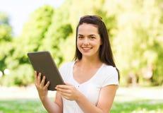 Chica joven sonriente con la PC de la tableta que se sienta en hierba Imagen de archivo libre de regalías