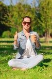 Chica joven sonriente con la taza de café en parque Foto de archivo