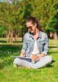 Chica joven sonriente con la taza del cuaderno y de café Foto de archivo