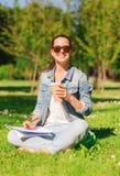 Chica joven sonriente con la taza del cuaderno y de café Foto de archivo libre de regalías