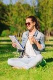 Chica joven sonriente con la taza del cuaderno y de café Fotografía de archivo libre de regalías