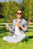 Chica joven sonriente con la taza del cuaderno y de café Imagenes de archivo