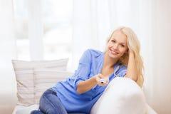 Chica joven sonriente con la TV teledirigida en casa Imagen de archivo libre de regalías